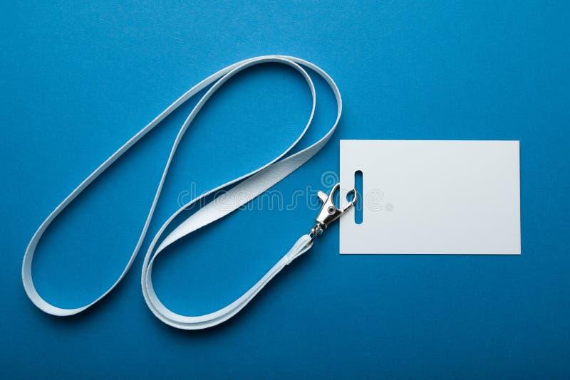 Κενό επιχειρησιακό διακριτικό που απομονώνεται στο μπλε υπόβαθρο Σαφής κενή χλεύη ετικεττών ονόματος που κλείνει το τηλέφωνο στο  στοκ φωτογραφία