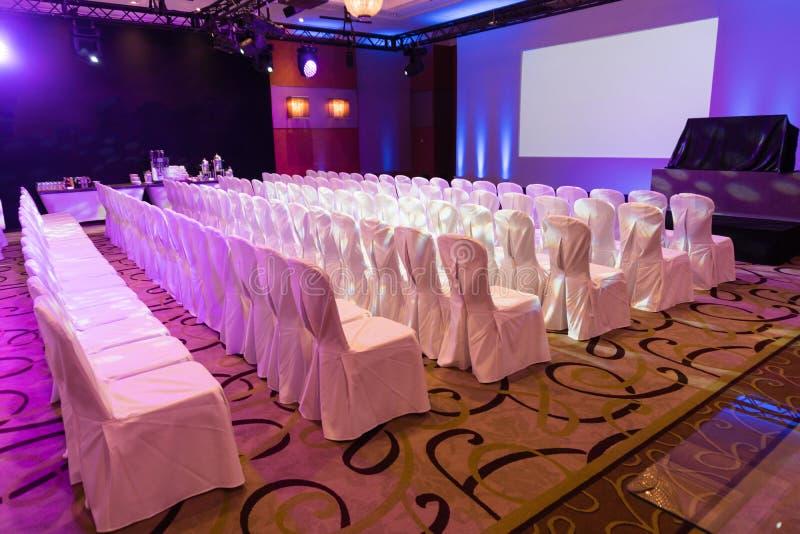 Κενό εσωτερικό της αίθουσας συνδιαλέξεων πολυτέλειας ή του δωματίου σεμιναρίου με την οθόνη προβολέων, άσπρες καρέκλες στοκ φωτογραφίες