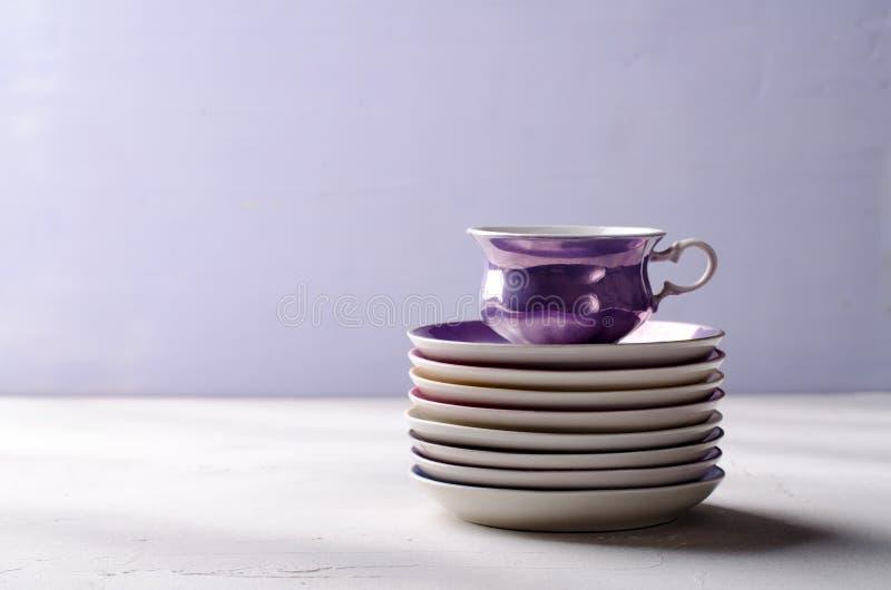 Κενό ζωηρόχρωμο επιτραπέζιο σκεύος πορσελάνης Ιώδες φλυτζάνι με τα πιάτα στο ιώδες υπόβαθρο στοκ εικόνες