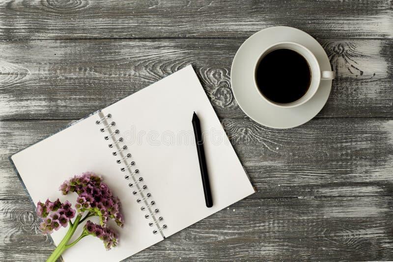 Κενό ημερολόγιο ή σημειωματάριο με ένα ελατήριο, ένα μολύβι και ένα ρόδινου λουλούδι φλιτζανιών του καφέ και σε έναν γκρίζο shabb στοκ φωτογραφίες με δικαίωμα ελεύθερης χρήσης