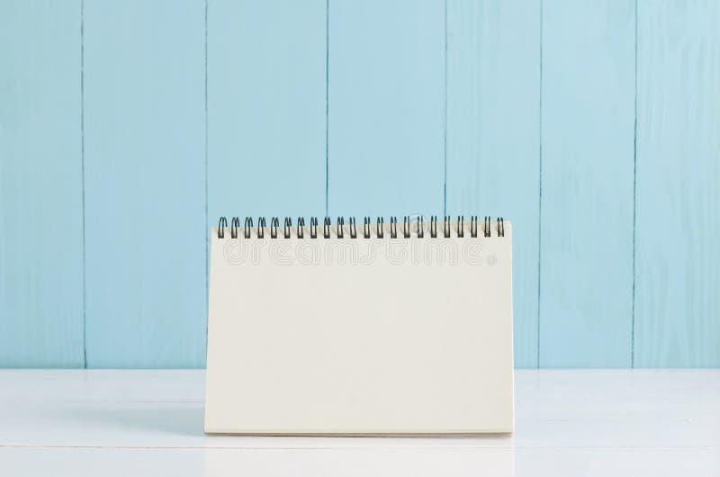 Κενό ημερολόγιο γραφείων στο άσπρο και μπλε ξύλινο υπόβαθρο στοκ εικόνες