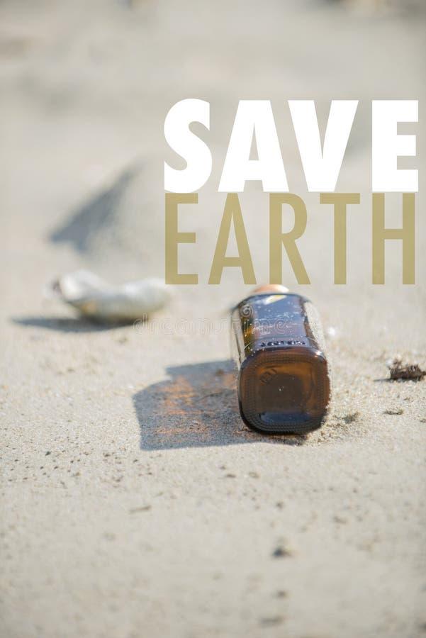 Κενό καφετί σαφές μπουκάλι με την ΚΑΠ που αφήνεται στην παραλία Εκτός από τη γη παρακαλώ! στοκ εικόνες