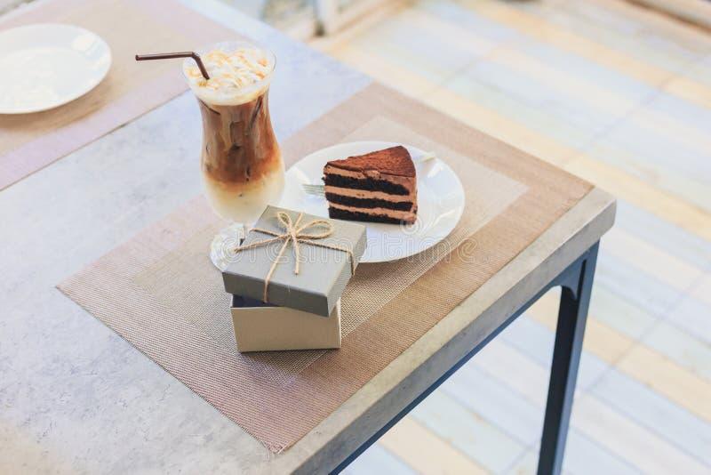 Κενό κιβώτιο δώρων κοντά στο κέικ στο τσάι πιάτων και γάλακτος είναι στον πίνακα Ένα παρόν στις διακοπές στοκ εικόνες