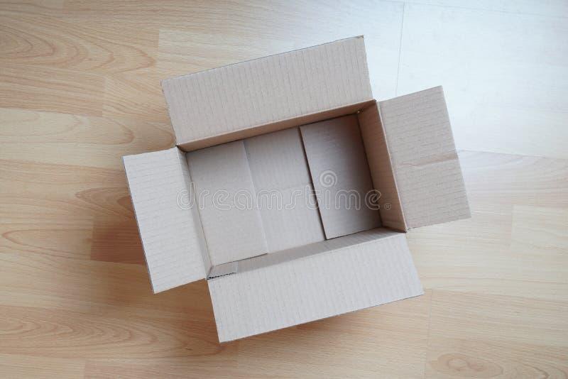 Κενό κουτί από χαρτόνι στο φυλλόμορφο πάτωμα στοκ φωτογραφία με δικαίωμα ελεύθερης χρήσης