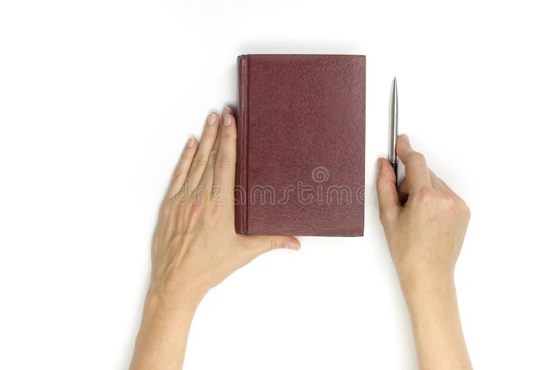 Κενό κόκκινο βιβλίο hardcover λαβής χεριών στο άσπρο υπόβαθρο στοκ φωτογραφίες