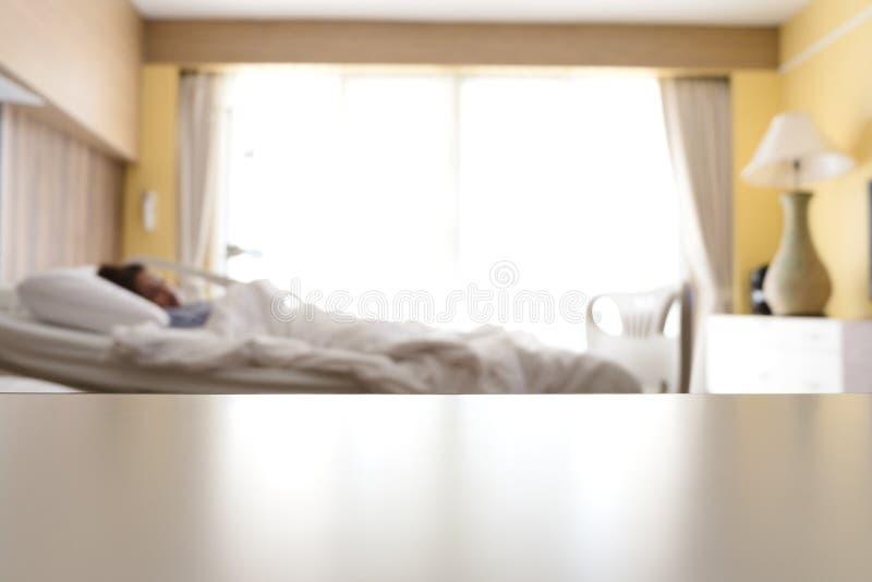 Κενό λευκό πέρα από το επιτραπέζιο υπόβαθρο νοσοκομείων κρεβατιών με το θολωμένο woma στοκ εικόνα με δικαίωμα ελεύθερης χρήσης