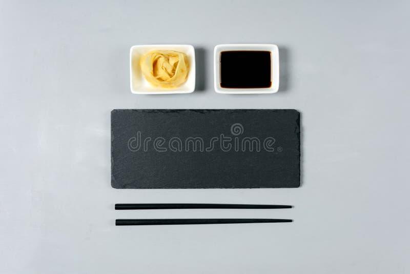 Κενό μαύρο πιάτο πλακών με chopstick στο γκρίζο ξύλινο υπόβαθρο Επίπεδος βάλτε Τοπ όψη φρέσκια ελιά πετρελαίου κουζινών τροφίμων  στοκ φωτογραφία