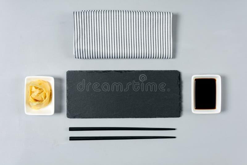 Κενό μαύρο πιάτο πλακών με chopstick στο γκρίζο ξύλινο υπόβαθρο Επίπεδος βάλτε Τοπ όψη φρέσκια ελιά πετρελαίου κουζινών τροφίμων  στοκ φωτογραφία με δικαίωμα ελεύθερης χρήσης