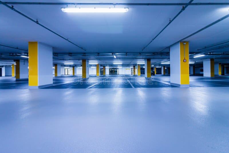 Κενό μπλε γκαράζ χώρων στάθμευσης με τις κίτρινες στήλες στοκ εικόνες