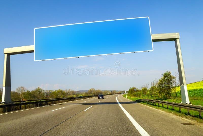 Κενό μπλε σημάδι αυτοκινητόδρομων πέρα από το δρόμο την ηλιόλουστη ημέρα στοκ φωτογραφίες
