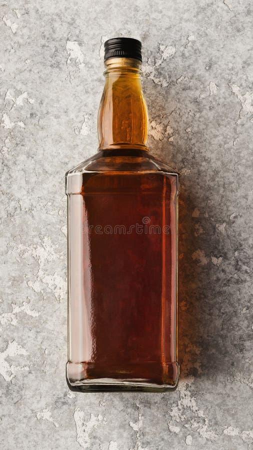 Κενό μπουκάλι με το ουίσκυ ή κονιάκ στο υπόβαθρο πετρών στοκ εικόνες