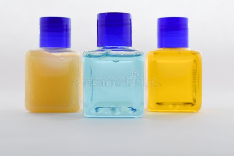 Κενό μπουκάλι, μπλε, πορτοκαλί, κίτρινο υγρό στοκ φωτογραφίες