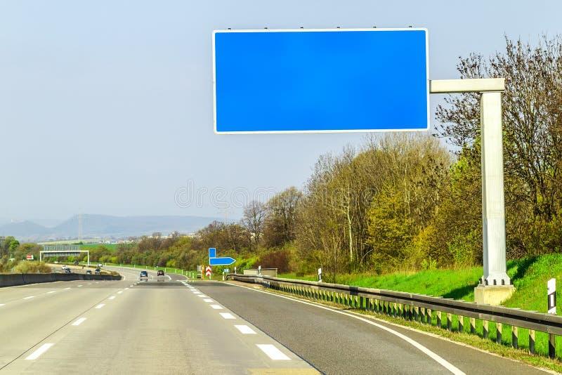 Κενό μπλε σημάδι αυτοκινητόδρομων πέρα από το δρόμο την ηλιόλουστη ημέρα στοκ εικόνες με δικαίωμα ελεύθερης χρήσης