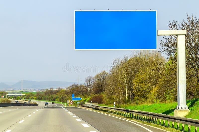 Κενό μπλε σημάδι αυτοκινητόδρομων πέρα από το δρόμο την ηλιόλουστη ημέρα στοκ εικόνα