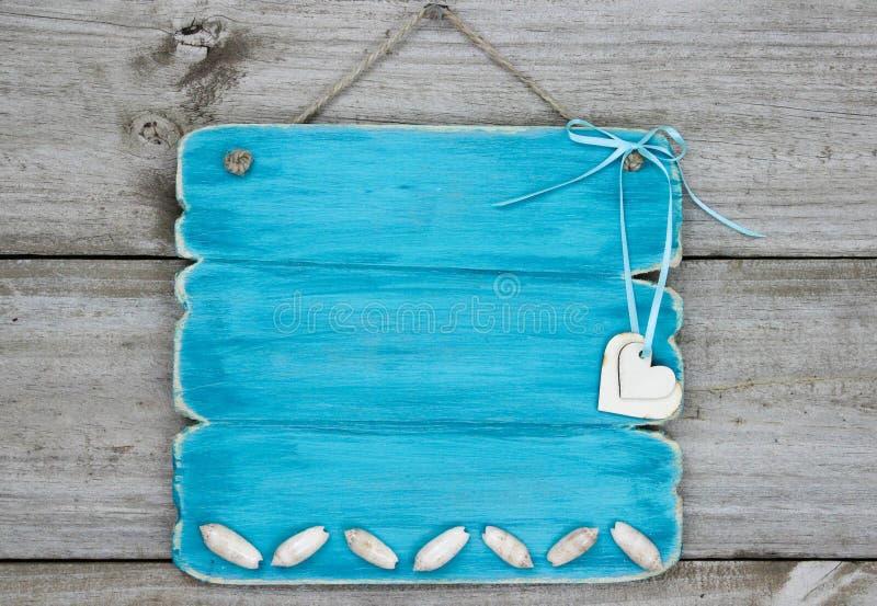 Κενό μπλε σημάδι κιρκιριών με τα θαλασσινά κοχύλια και τις καρδιές που κρεμούν στην αγροτική ξύλινη πόρτα στοκ εικόνα με δικαίωμα ελεύθερης χρήσης