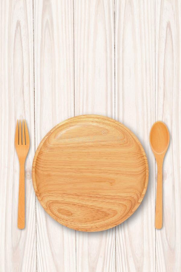 Κενό ξύλινο πιάτο με το δίκρανο κουταλιών στον ξύλινο πίνακα στοκ φωτογραφίες με δικαίωμα ελεύθερης χρήσης