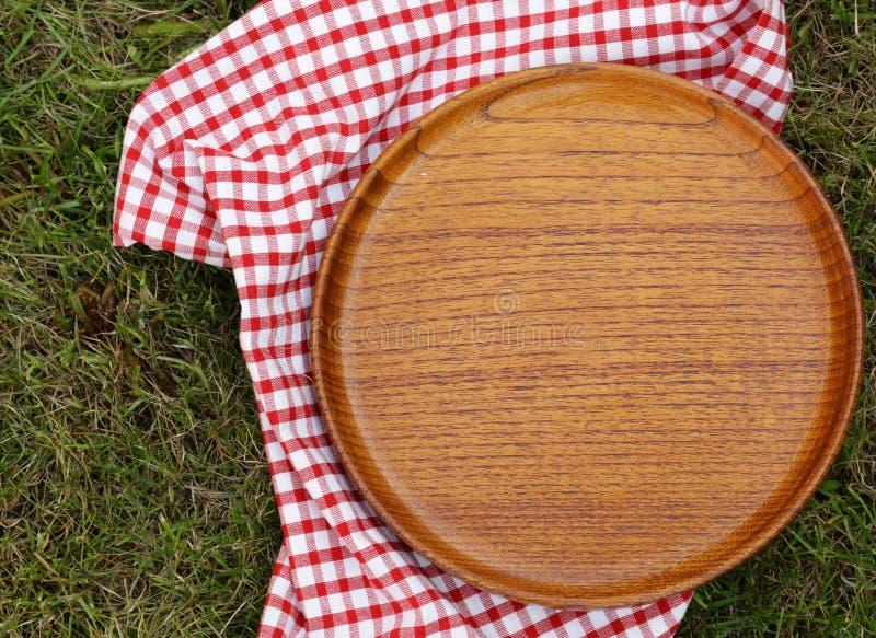 Κενό ξύλινο πιάτο στην πράσινη χλόη στοκ εικόνα με δικαίωμα ελεύθερης χρήσης