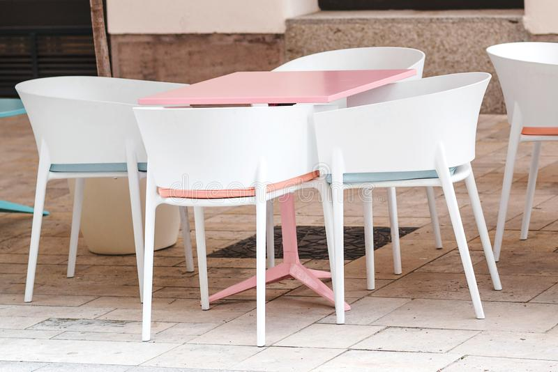 Κενό πεζούλι καφέ και εστιατορίων με το ρόδινο πίνακα και τις άσπρες καρέκλες Καφές στην οδό Θερινό πεζούλι στην Ευρώπη Υπαίθριος στοκ εικόνα με δικαίωμα ελεύθερης χρήσης