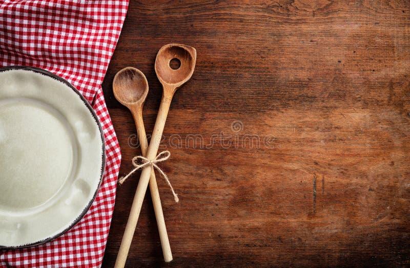 Κενό πιάτο, εργαλεία κουζινών και κόκκινο τραπεζομάντιλο στον ξύλινο πίνακα, τοπ άποψη, διάστημα αντιγράφων στοκ εικόνα