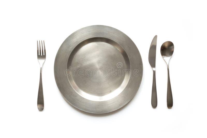 Κενό πιάτο μετάλλων με το μαχαίρι και δίκρανο στο υπόβαθρο πλακών, με το διάστημα αντιγράφων Επιτραπέζια ρύθμιση στοκ εικόνες με δικαίωμα ελεύθερης χρήσης