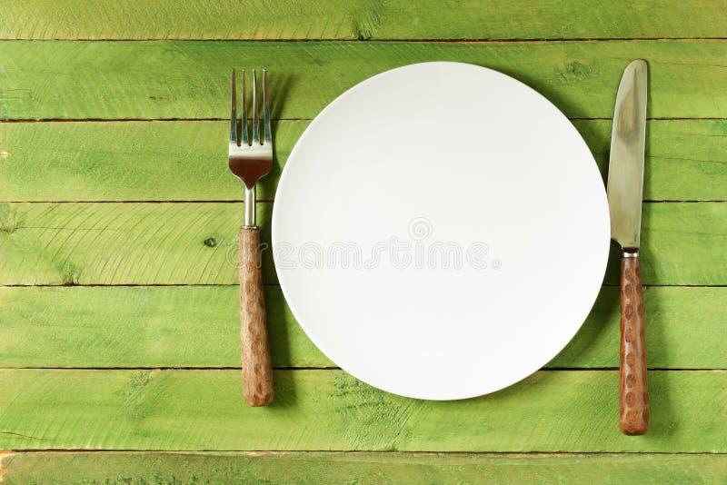 Κενό πιάτο με τα μαχαιροπήρουνα και την πετσέτα στοκ εικόνα
