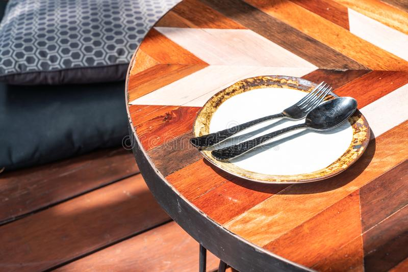 κενό πιάτο με το κουτάλι και δίκρανο στον πίνακα στοκ εικόνες