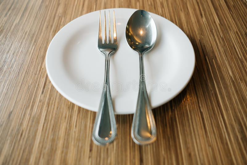 Κενό πιάτο με το κουτάλι και δίκρανο σε ξύλινο στοκ εικόνες