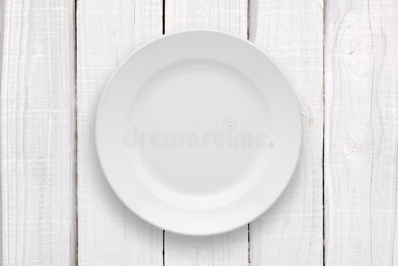 Κενό πιάτο στον άσπρο πίνακα στοκ εικόνα