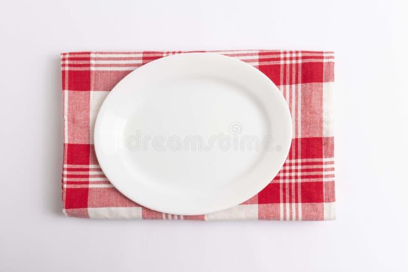 Κενό πιάτο στο κόκκινο ελεγμένο κλωστοϋφαντουργικό προϊόν στοκ φωτογραφία με δικαίωμα ελεύθερης χρήσης