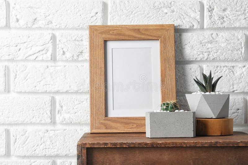 Κενό πλαίσιο και succulent εγκαταστάσεις στο ξύλινο γραφείο κοντά στον άσπρο τουβλότοιχο, διάστημα για το σχέδιο r στοκ εικόνες