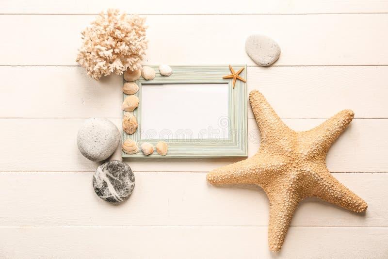 Κενό πλαίσιο με τα κοχύλια, τους αστερίες και τις πέτρες θάλασσας στο άσπρο ξύλινο υπόβαθρο στοκ εικόνα με δικαίωμα ελεύθερης χρήσης