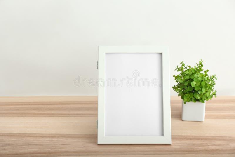 Κενό πλαίσιο φωτογραφιών και houseplant στον πίνακα ενάντια στον άσπρο τοίχο στοκ φωτογραφίες με δικαίωμα ελεύθερης χρήσης