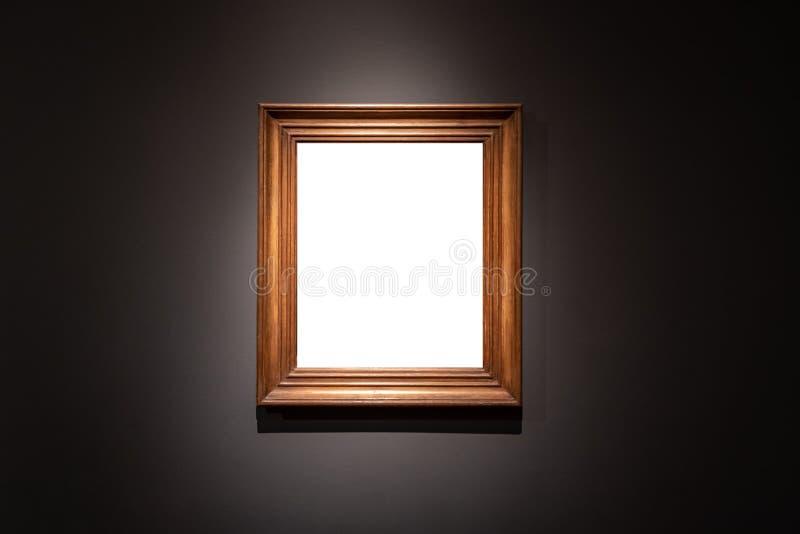Κενό που κρεμά το μεμονωμένο πλαίσιο σε ένα μαύρο υπόβαθρο γκαλεριών τέχνης στοκ φωτογραφία