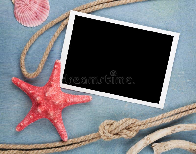 Κενό πλαίσιο φωτογραφιών με τα θαλασσινά κοχύλια, σχοινί σκαφών, πέτρες θάλασσας στοκ φωτογραφία