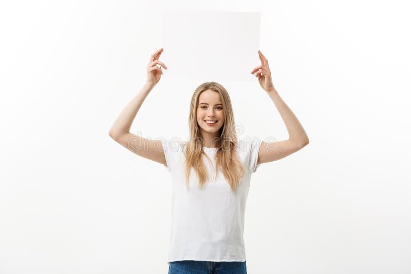 κενό σημάδι Γυναίκα που κρατά το κενό κενό άσπρο σημάδι επάνω από το κεφάλι της Συγκινημένη και ευτυχής όμορφη νέα γυναίκα που απ στοκ εικόνα με δικαίωμα ελεύθερης χρήσης