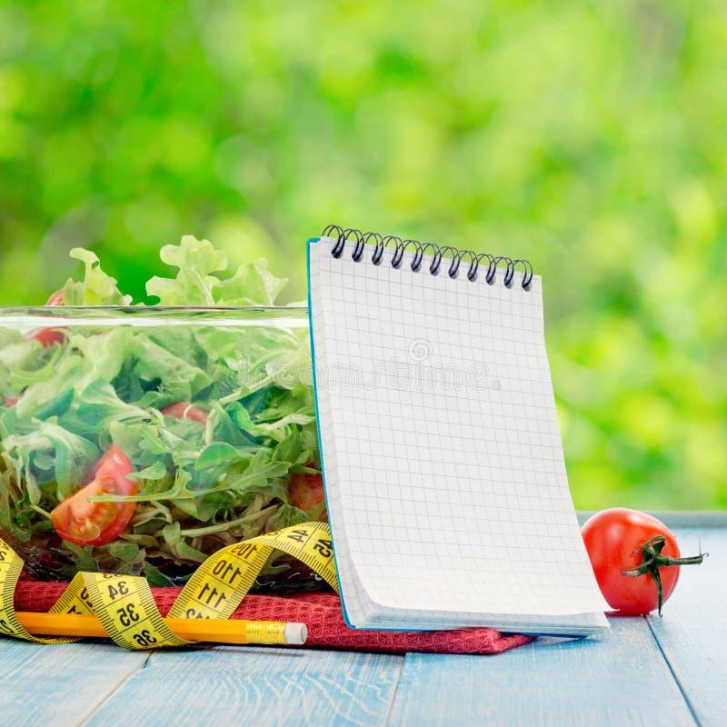 Κενό σημειωματάριο με το μεγάλο κύπελλο της σαλάτας και της μέτρησης της ταινίας στοκ φωτογραφία