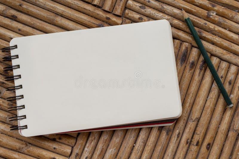 Κενό σημειωματάριο με το μολύβι στον αγροτικό ξύλινο πίνακα Σπειροειδές σημειωματάριο με τη Λευκή Βίβλο για το μήνυμα ή το σχέδιο στοκ εικόνα