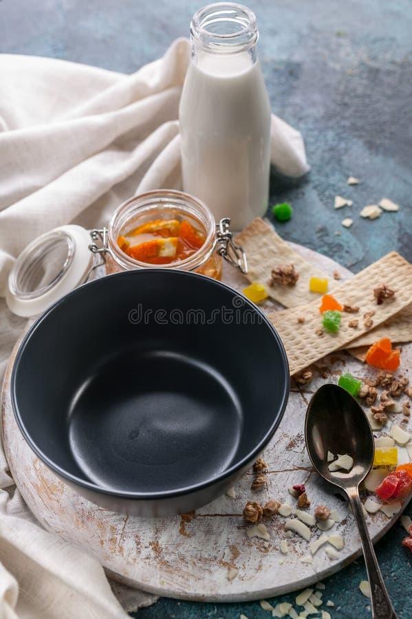 Κενό σκοτεινό κύπελλο, γλασαρισμένα φρούτα, πορτοκαλιά μαρμελάδα και γάλα Νόστιμη και υγιής έννοια προγευμάτων r στοκ εικόνα