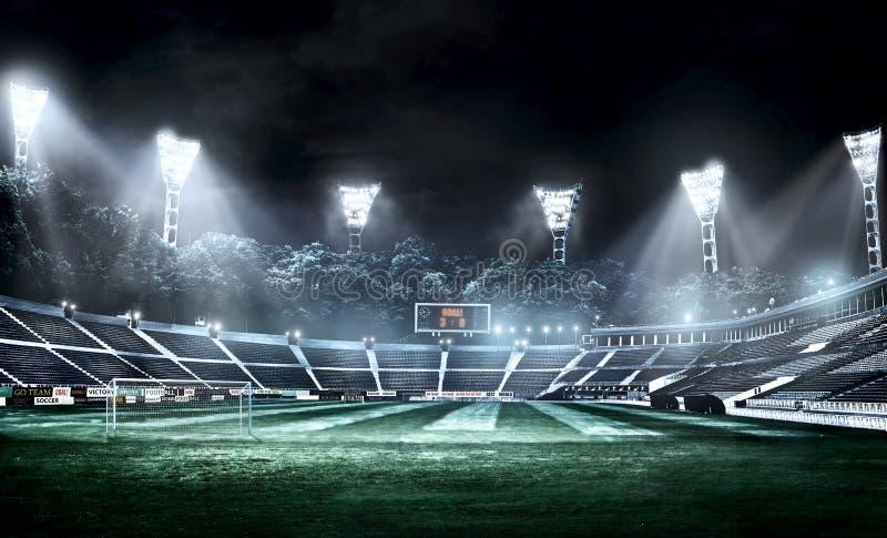 Κενό στάδιο ποδοσφαίρου στην ελαφριά τρισδιάστατη απεικόνιση ακτίνων τη νύχτα στοκ εικόνες