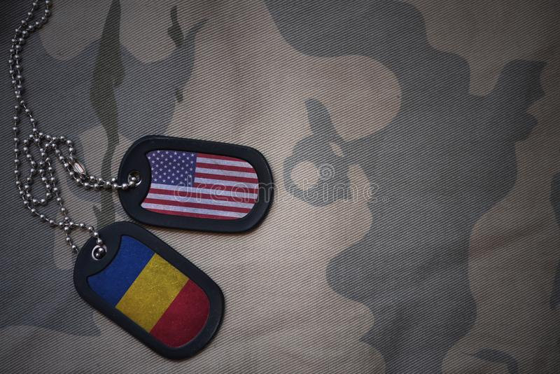 κενό στρατού, ετικέττα σκυλιών με τη σημαία των Ηνωμένων Πολιτειών της Αμερικής και της Ρουμανίας στο χακί υπόβαθρο σύστασης στοκ φωτογραφίες