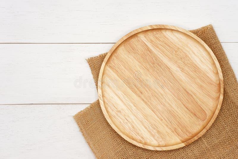 Κενό στρογγυλό ξύλινο πιάτο με το αγροτικό καφετί burlap ύφασμα στον άσπρο ξύλινο πίνακα στοκ εικόνα
