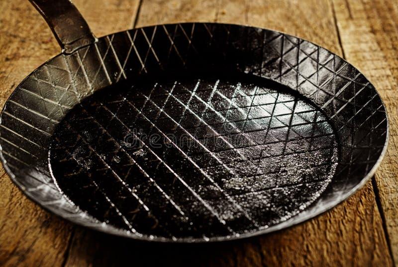 Κενό τηγάνι χυτοσιδήρου στον πίνακα στοκ φωτογραφία με δικαίωμα ελεύθερης χρήσης