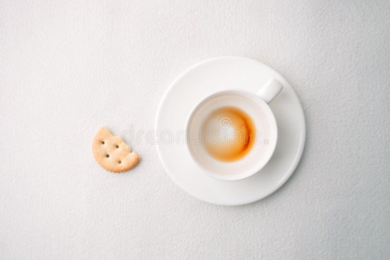Κενό φλυτζάνι καφέ μετά από το ποτό και τριζάτο πρόχειρο φαγητό στο άσπρο υπόβαθρο, καθιερώνουσα τη μόδα ελάχιστη μονοχρωματική έ στοκ φωτογραφίες
