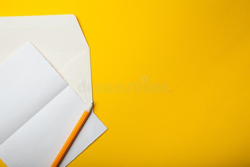 Κενό φύλλο για την επιστολή και φάκελος σε ένα κίτρινο υπόβαθρο r στοκ εικόνα