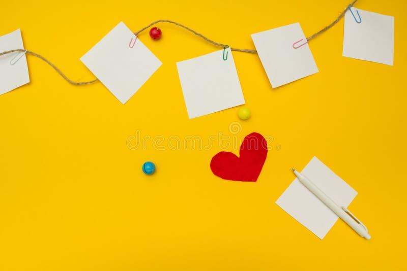 Κενό φύλλο εγγράφου σε ένα κίτρινο υπόβαθρο Έγγραφο σημειώσεων για το σχοινί Ο βαλεντίνος στέλνει το μήνυμα αγάπης κειμένων στοκ εικόνα