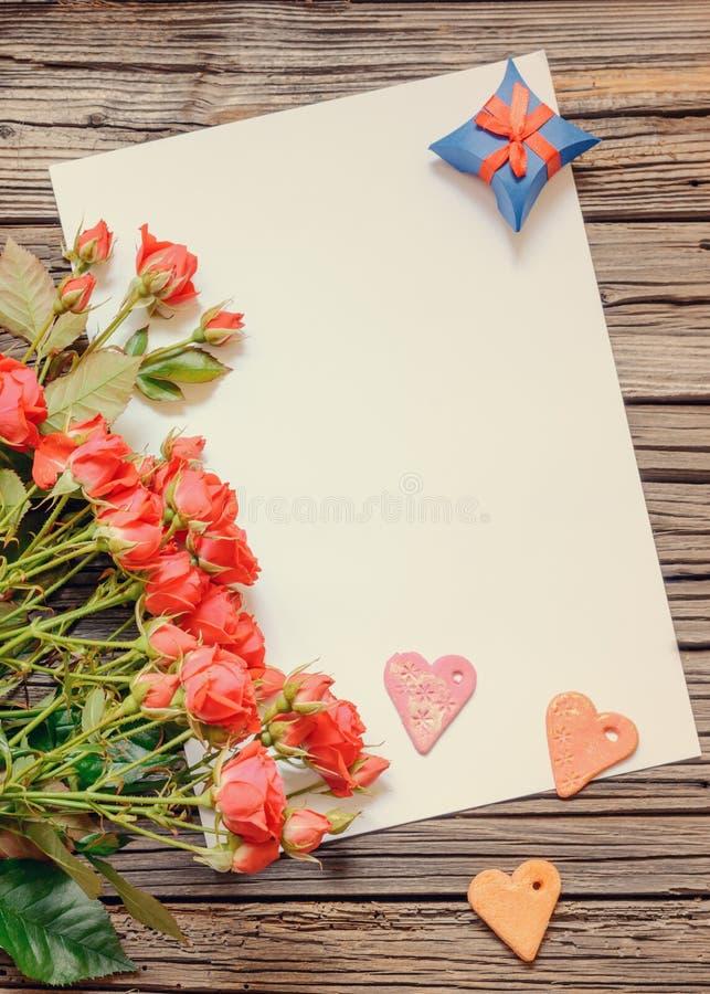Κενό φύλλο του εγγράφου για την ξύλινη επιφάνεια με τα τριαντάφυλλα στοκ φωτογραφία