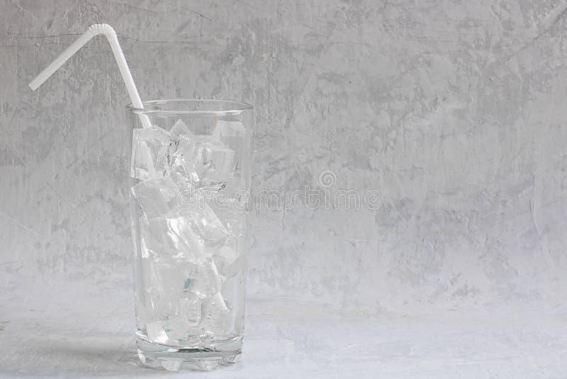 Κενό ψηλό γυαλί με τους κύβους πάγου και άχυρο έτοιμο να χύσει το κρύο θερινό ποτό στο γκρίζο υπόβαθρο τσιμέντου με το διάστημα α στοκ φωτογραφία με δικαίωμα ελεύθερης χρήσης