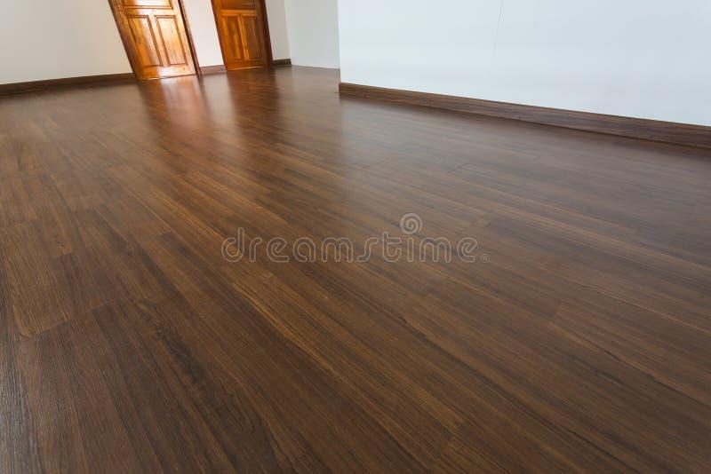 Κενό δωμάτιο, άσπρο υπόβαθρο τοίχων κονιάματος και ξύλινο φυλλόμορφο πάτωμα στοκ εικόνα