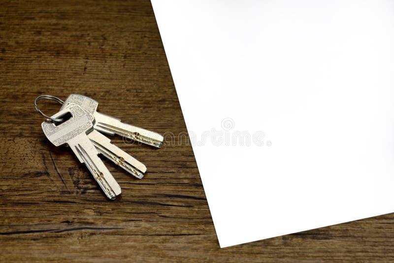 Κενό Indenture ή σύμφωνου ή συμβάσεων για το μίσθωμα διαμέρισμα και 3 ασημένια κλειδιά στον ξύλινο πίνακα στοκ φωτογραφίες