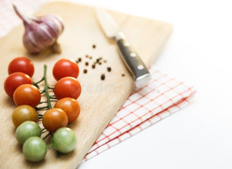 Κεράσι ντοματών με το σκόρδο και μαύρο πιπέρι στον ξύλινο πίνακα Διαφορετικοί βαθμοί ripeness του κερασιού ντοματών στοκ φωτογραφία με δικαίωμα ελεύθερης χρήσης